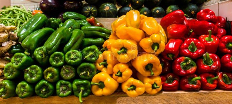Gröna, gula och röda peppar på ett stånd royaltyfri fotografi
