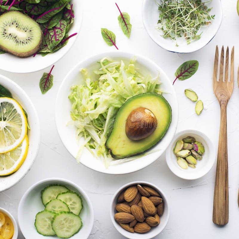 Gröna ingredienser för vårdetoxsallader: spenat syra med röda åder, gurkor, rädisor, isberggrönsallat som är grön arkivbild