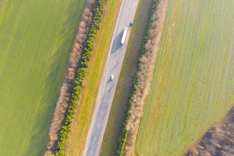 Gröna jordbruksmarker som omger flyg- sikt för huvudväg lantlig liggande royaltyfri foto