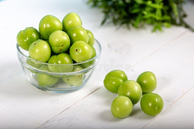 Gröna körsbärsröda plommoner i exponeringsglasbunke på trätabellen royaltyfri bild