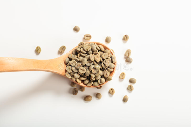 Gröna kaffebönor i en träsked arkivbild