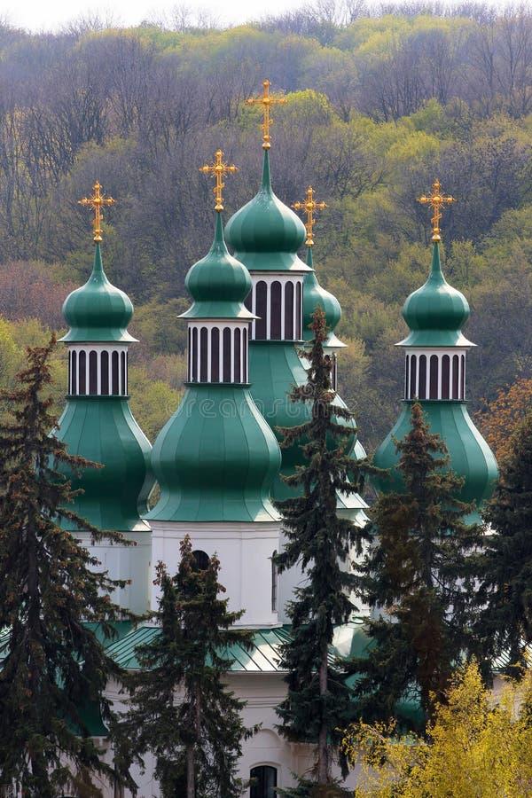 Gröna kupoler av kyrkan för helig Treenighet på den Kitaevo kloster i Kiev, Ukraina arkivfoton