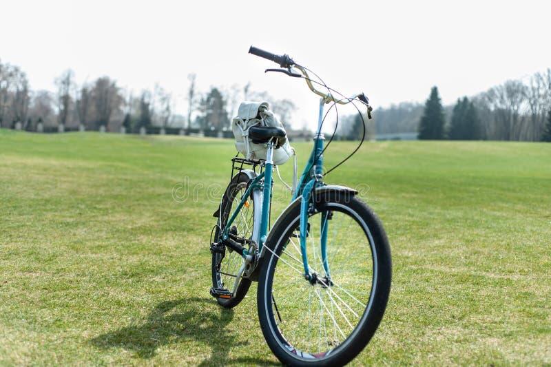 Gröna kvinnors cykel med den lilla vita ryggsäcken på dess stamstag på grönt gräs, tidig vår arkivfoton