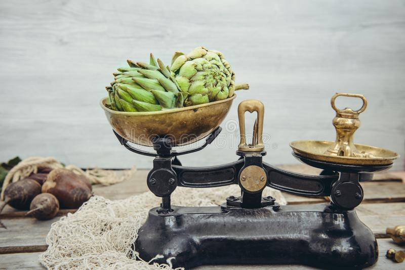 Gröna läckra kronärtskockagrönsaker på tappningvikterna som står på den lantliga träbakgrunden Lokal marknadsräknare för bonde royaltyfri foto
