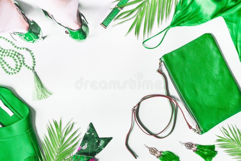 Gröna modekläder och tillbehör till platt klädsel Handväska, jacka, smycken och bälte med tropiska blad och ben av honkön i royaltyfri fotografi