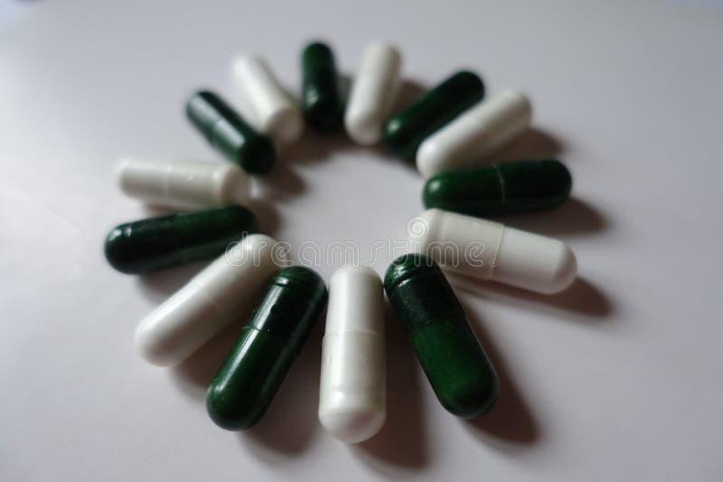 Gröna multivitamins och vita magnesiumkapslar i en cirkel royaltyfri fotografi