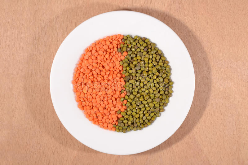 Gröna mung bönor och röd rå lins på den vita plattan royaltyfri fotografi