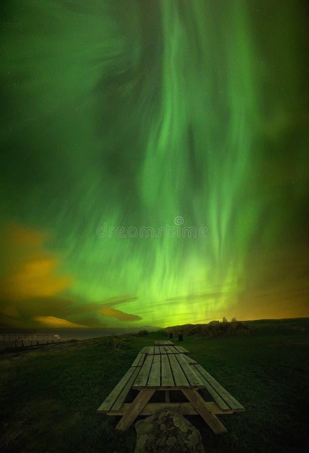 Gröna nordliga ljus på natthimlen ovanför picknickområde i den Ranheim stranden, Norge royaltyfri bild