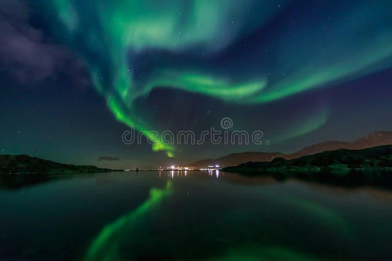 Gröna nordliga ljus som reflekterar i sjön med berg och arkivbild