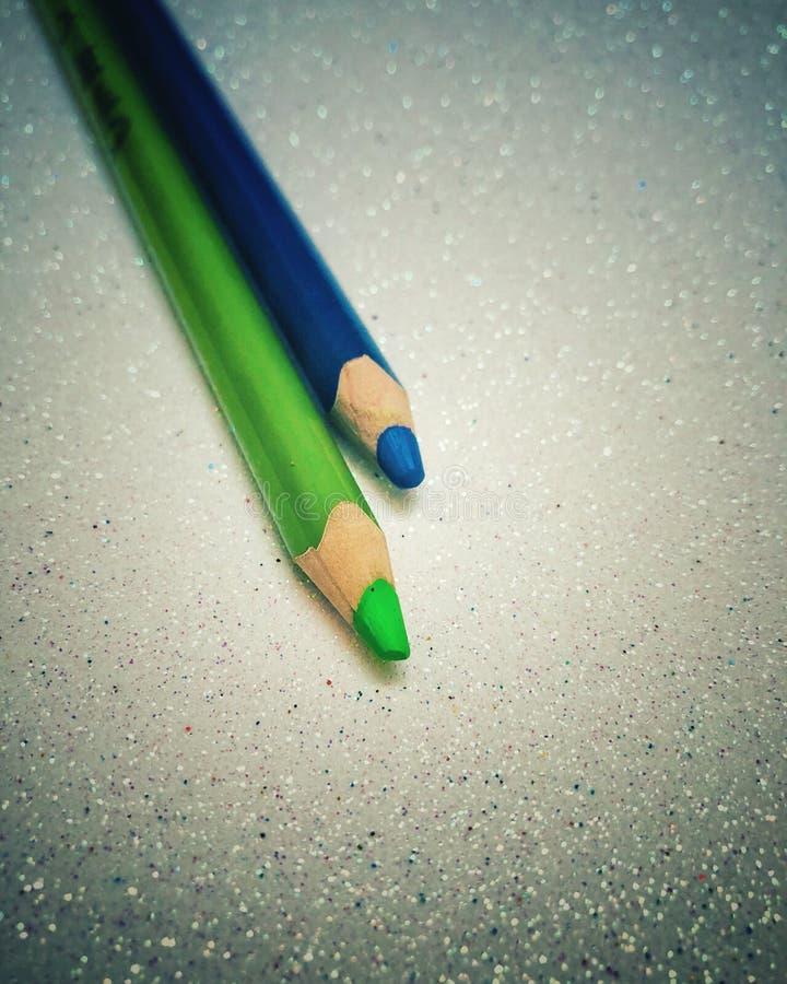 Gröna och blåa färgpennor arkivbilder