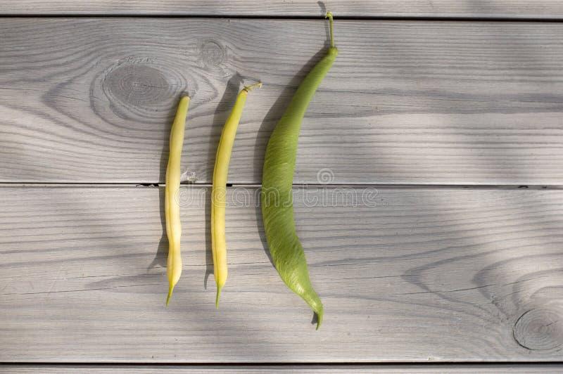 Gröna och gula bönor på en grå trätabell arkivbilder