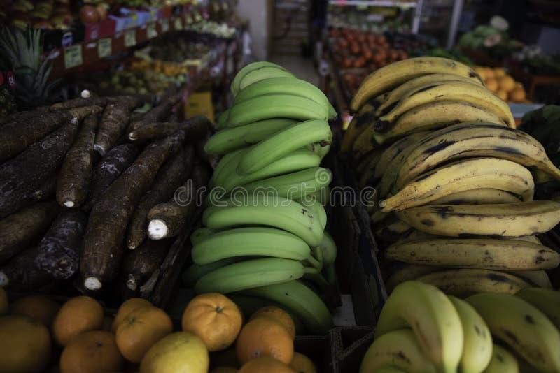 Gr?na och gula bananer i fruktaff?r royaltyfri foto