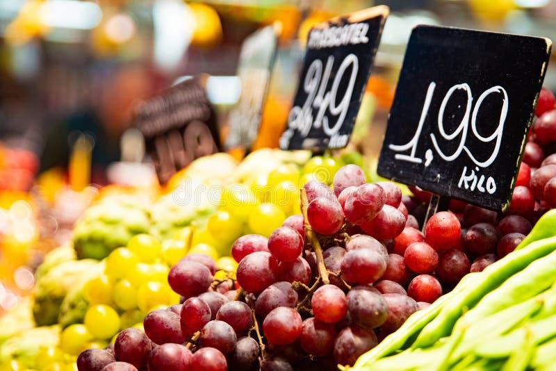 Gröna och purpurfärgade druvor på grönsak- och fruktstånd royaltyfria foton