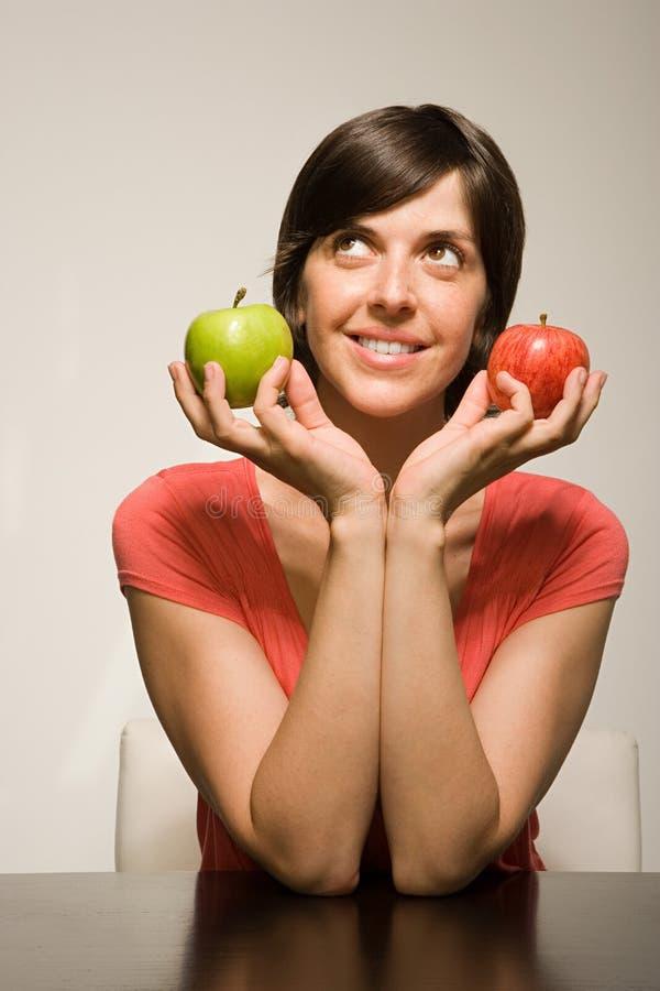 Gröna och röda äpplen för kvinnainnehav royaltyfri fotografi