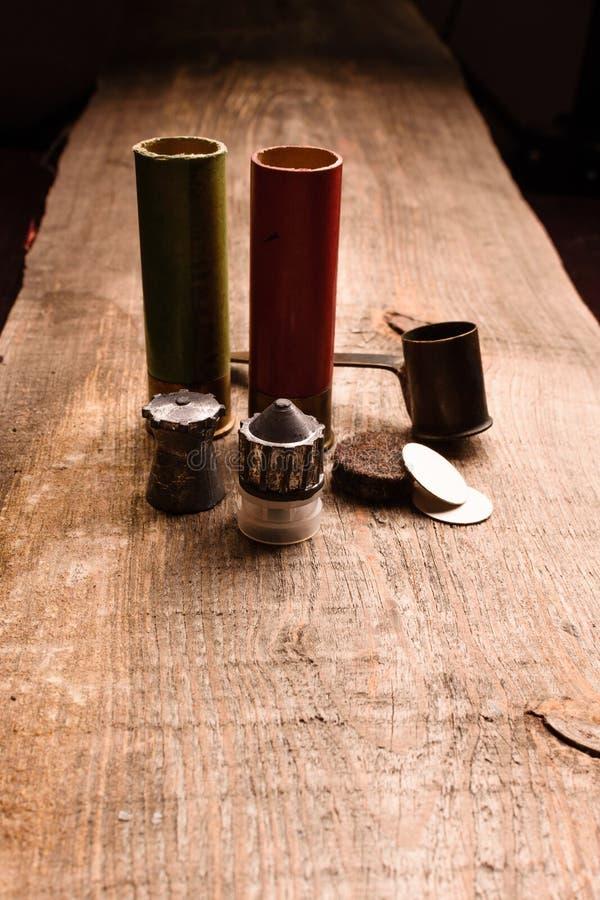Gröna och röda jaktskal med tillbehör är på en träst arkivbild