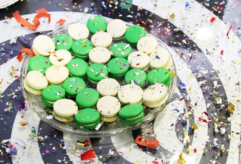 Gröna och vita makron i det glass magasinet med konfettier fotografering för bildbyråer