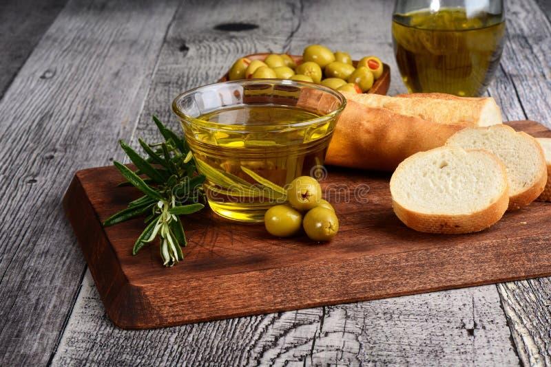 Gröna oliv för Closeup med olja och nytt bröd arkivfoto