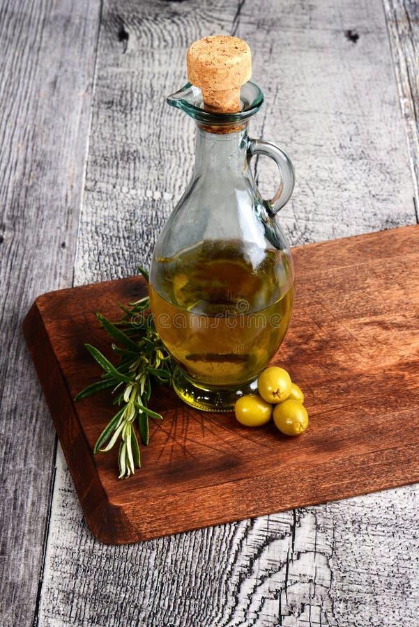 Gröna oliv med flaskan av olja och örter arkivbild