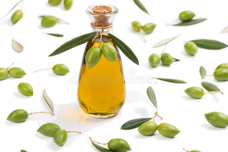 Gröna oliv och buteljerar av olivolja arkivbild
