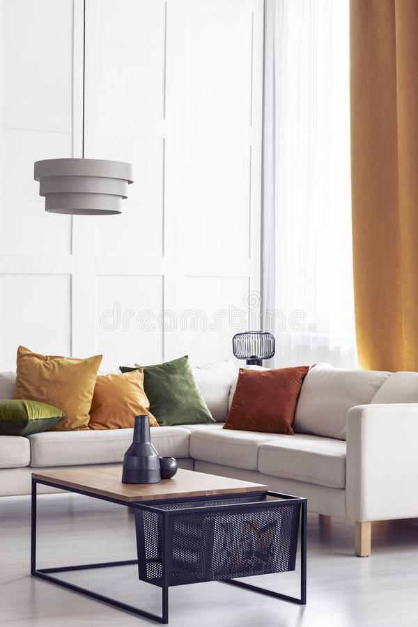 Gröna, orange och gula kuddar på den vita hörnsoffan i stilfull vardagsrum, verkligt foto med kopieringsutrymme arkivbilder