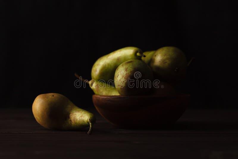 Gröna päron på mörk bakgrund för trätabell, främre sikt royaltyfri fotografi