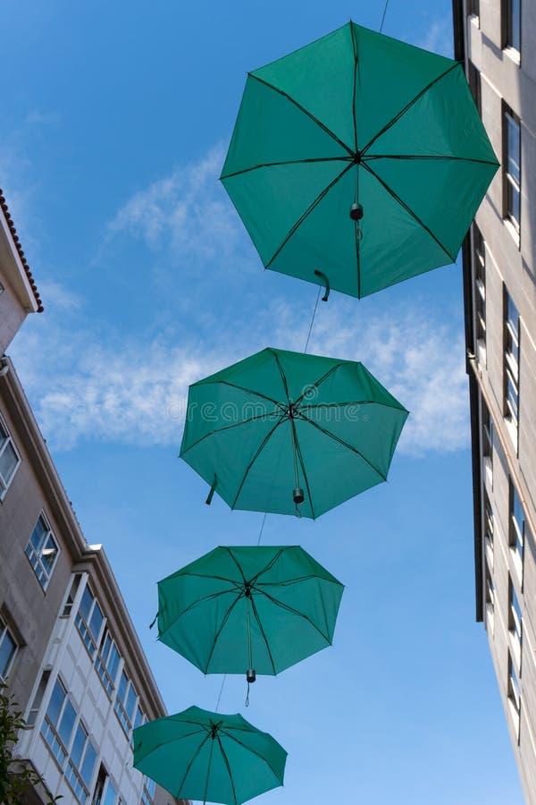 Gröna paraplyer som hänger längs gatan royaltyfria foton