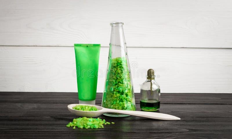 Gröna produkter för sammansättningsskönhetbehandling i gröna färger: schampo tvål, salt för bad, olja royaltyfri bild