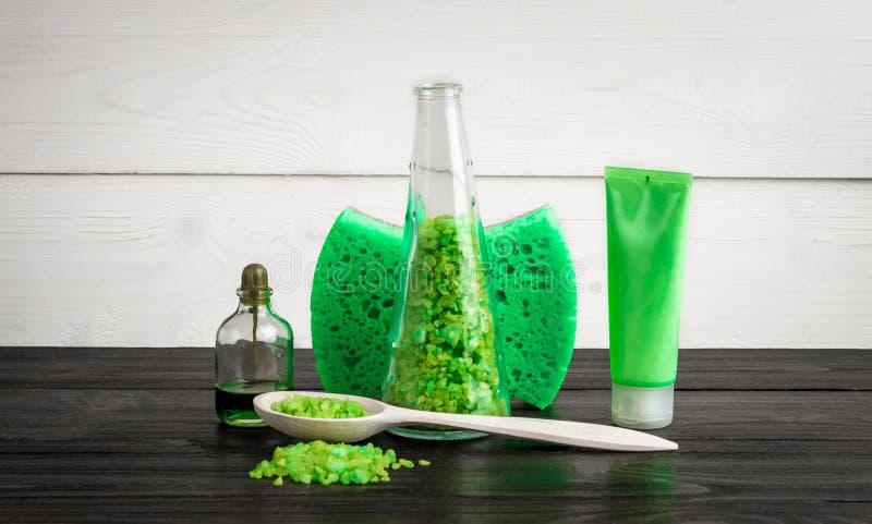 Gröna produkter för sammansättningsskönhetbehandling i gröna färger: schampo tvål, salt för bad, olja royaltyfria bilder