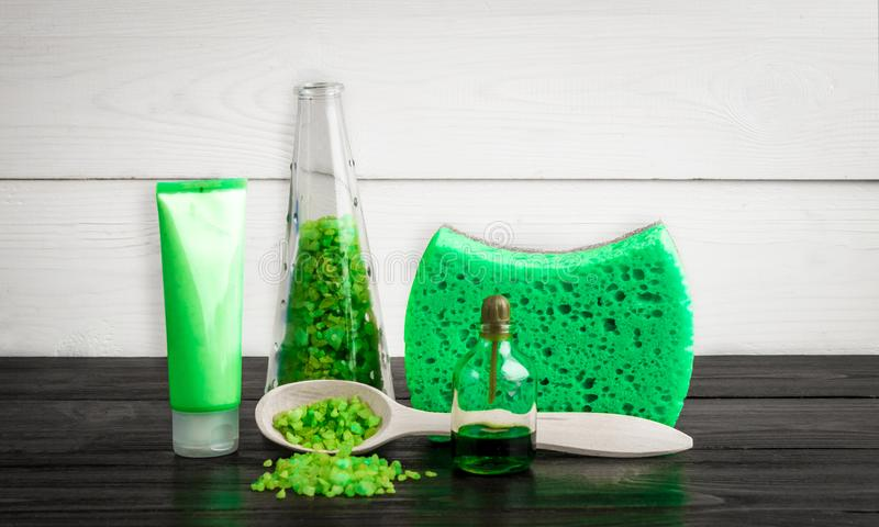 Gröna produkter för sammansättningsskönhetbehandling i gröna färger: schampo tvål, salt för bad, olja arkivbild