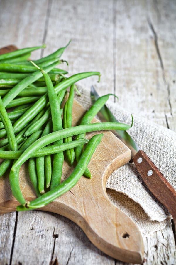 Gröna radbönor och kniv arkivfoto