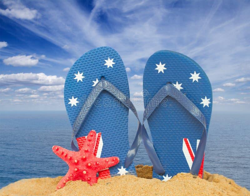 Gröna sandaler och sjöstjärna i sand arkivfoton