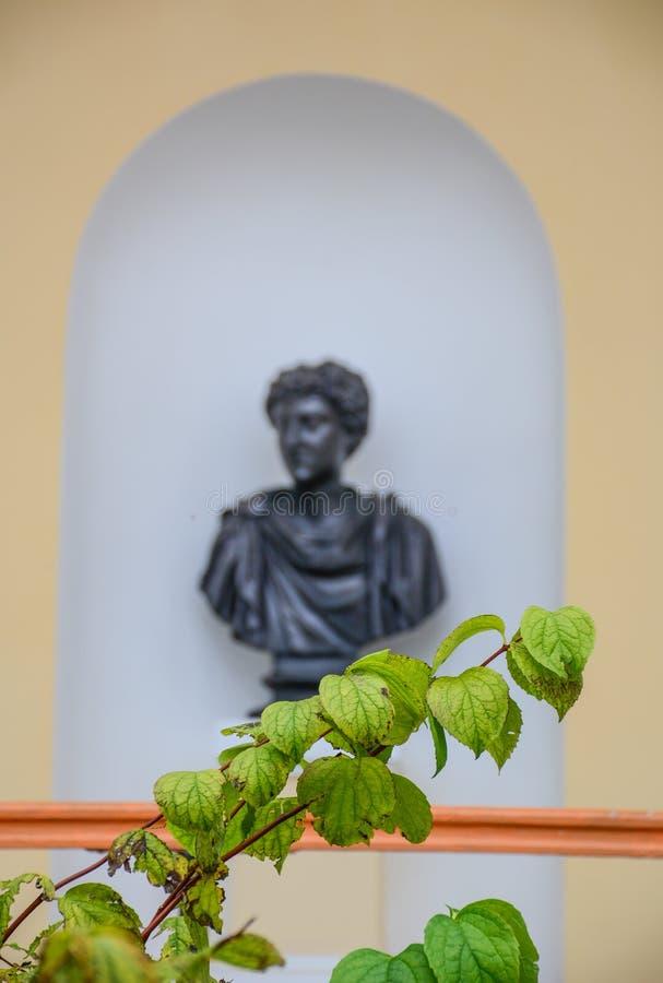 Gröna sidor med brons statybakgrund arkivfoto