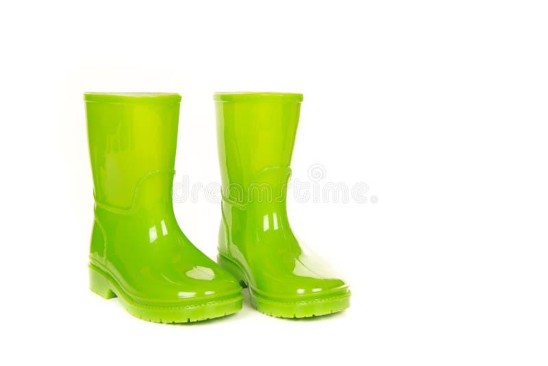 Gröna skinande barnregnkängor arkivfoton
