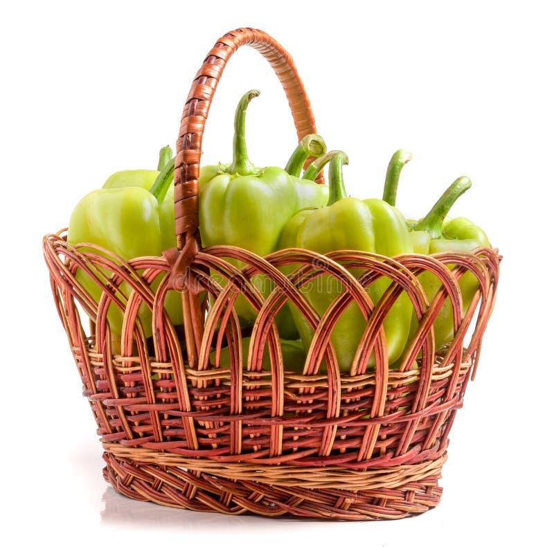 Gröna spanska peppar i en vide- korg som isoleras på vit bakgrund royaltyfri bild