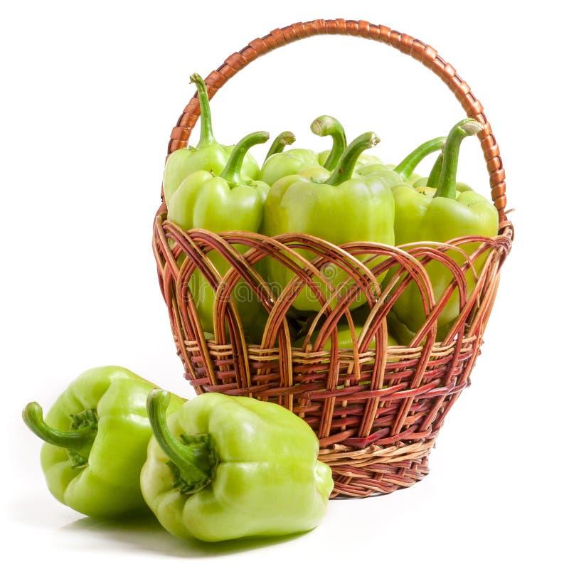 Gröna spanska peppar i en vide- korg som isoleras på vit bakgrund royaltyfri foto