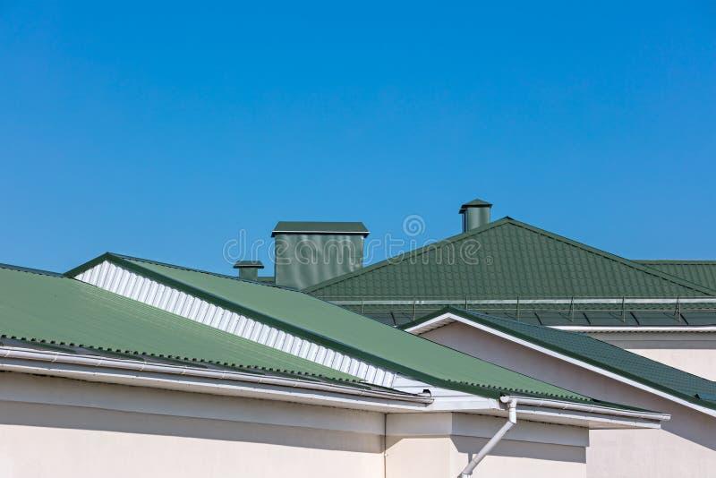 Gröna tak av hus med nya stuprännor på bakgrund för blå himmel royaltyfri bild