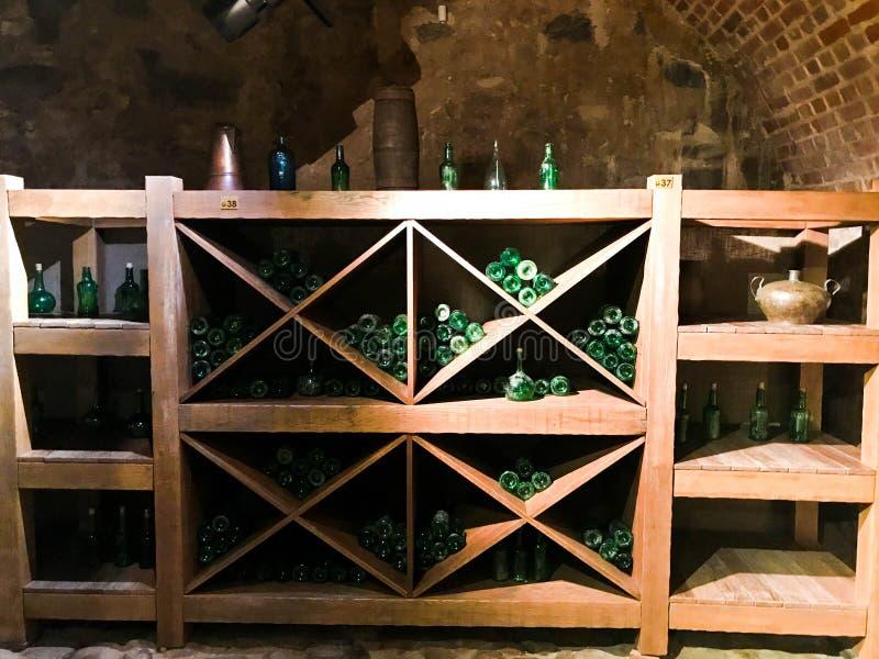 Gröna tomma vin- och ölglasflaskor för tappning i ett vinskåp med hyllor i en gammal medeltida bricked stenkällare arkivbilder