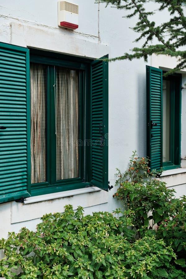 Gröna träslutare på det vita stuckaturhuset, Grekland arkivfoto