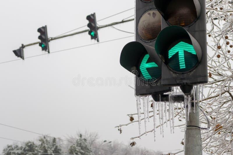 Gröna trafikljus för framåt och vänstra vänd, med istappar som haging från dem, under vintersäsong, efter dagar av kallt regn royaltyfria bilder