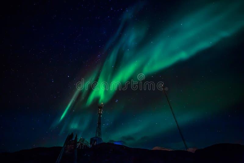 Gröna vågor av Aurora Borealis med glänsande stjärnor över monteringen royaltyfri foto