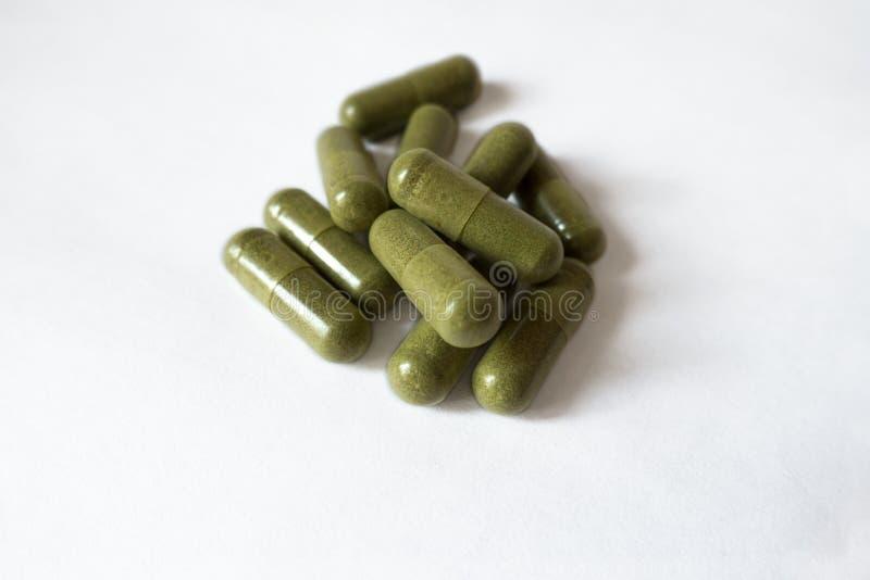 Gröna vitaminkapslar för handfull på vit bakgrund fotografering för bildbyråer