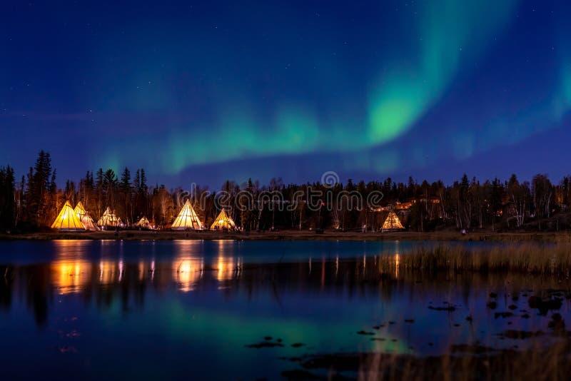 Grönaktiga Aurora Borealis över den upplysta tipin nära en sjö, gul kniv arkivfoton