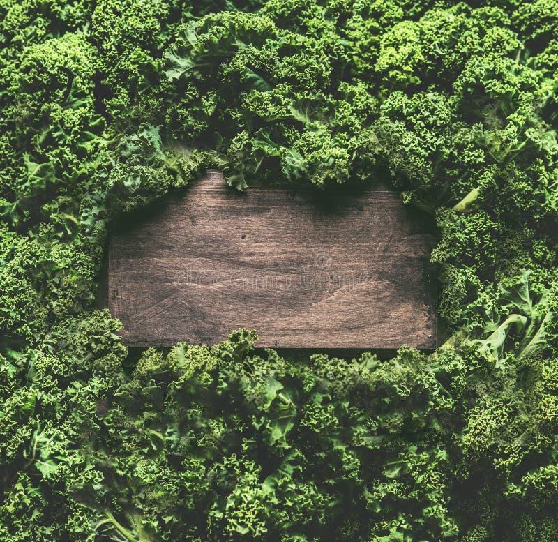 Grönkål lämnar bakgrundsramen med trätecknet Sunda detoxgrönsaker Rent äta och banta begrepp Bästa sikt med kopian arkivfoto