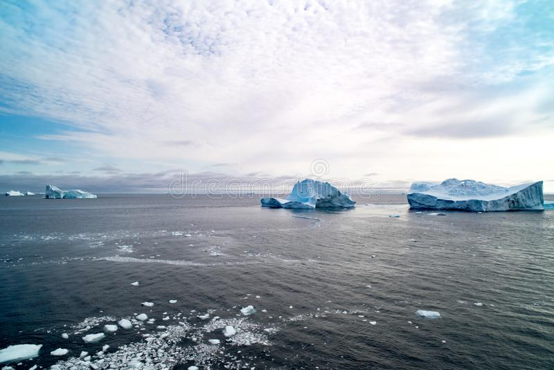 Grönländsk blå himmel med altocumulusmoln över mörkt - blått arktiskt hav med isberg och isisflak, Grönland royaltyfria bilder