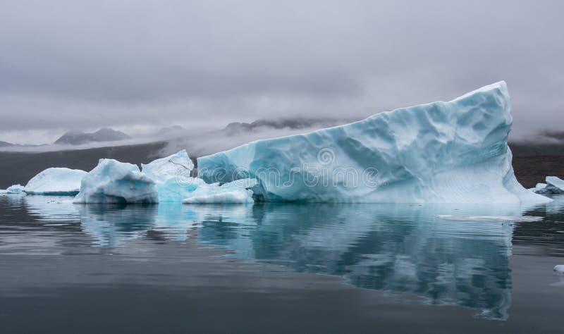 Grönland, blauer Eisberg mit perfekter Reflexion im Fjord mit drastischer Stimmung des Himmels stockfoto