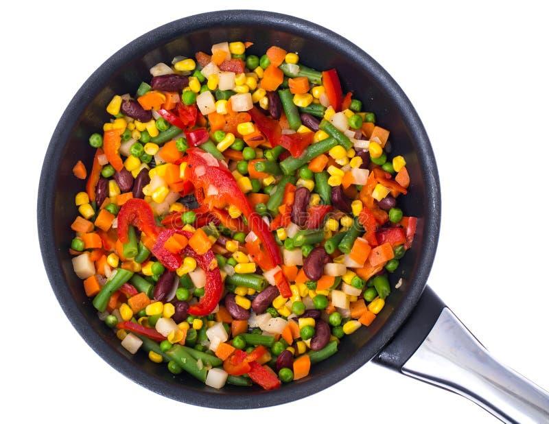 Grönsak som är blandad med bönor och havre i stekpannan, bästa sikt som isoleras på vit arkivfoto