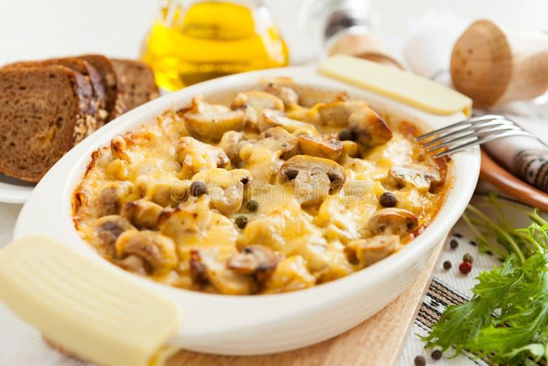 Grönsakcasserole med champinjoner och ost arkivfoto