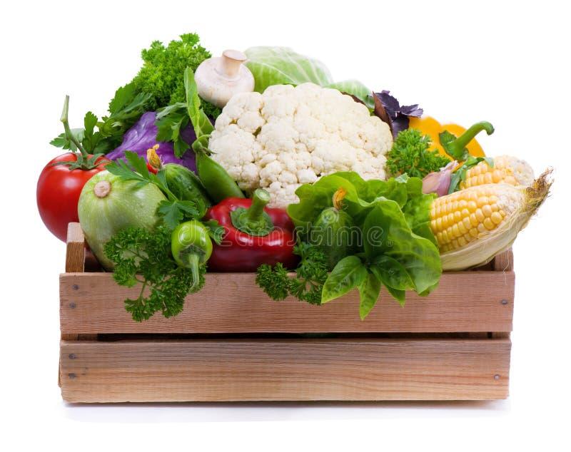 Grönsaker i träask isoleras på vit royaltyfri foto