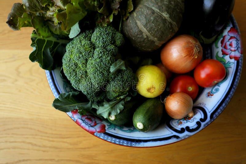 Grönsaker inklusive broccoli, pumpa, lökar, tomater, zucchinier, aubergine, grönsallat, citroner i bunke på en träbakgrund royaltyfria foton