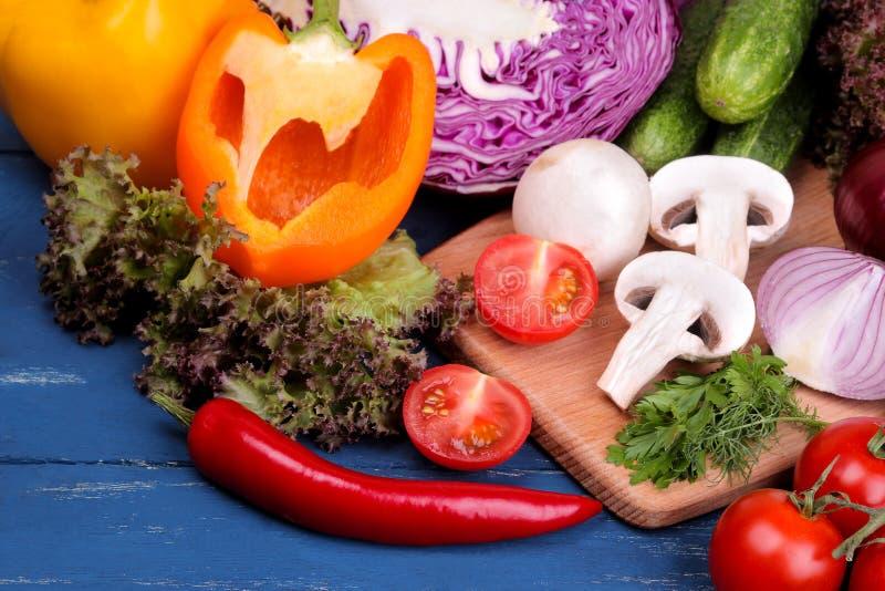 Grönsaker inklusive löken för vitlökgurkakål pepprar rödbetamorotzucchinin och tomater på en blå trätabell royaltyfri bild